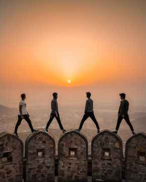 four men standing on arched stone walls with the view of the setting sun over a city