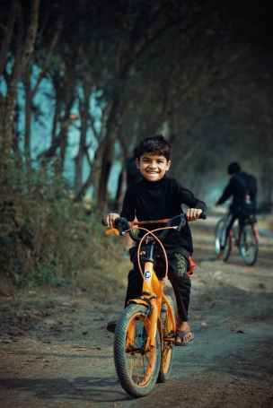 photo of boy riding bicycle