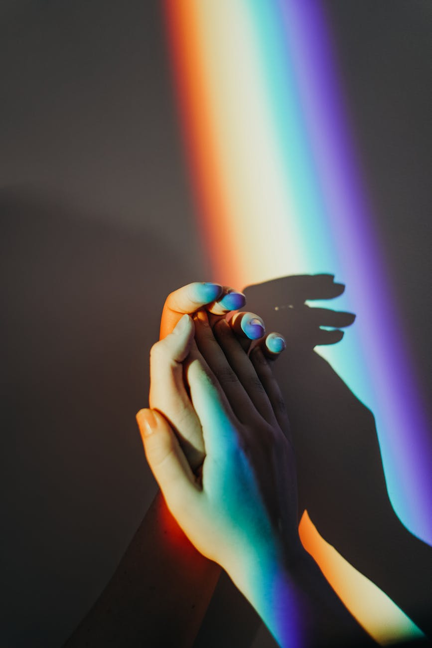 persons hands with rainbow colors